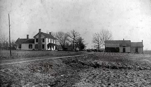Rural landscape. A plowed field in foreground. Beyond is a two-story farmhouse on a country road. Across the road is a one story frame building,.