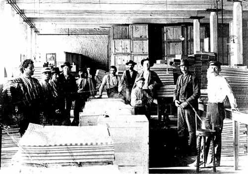 A dozen work force in the cloth room with large stacks of gingham on tables and floor.