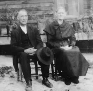 Elderly couple seated in the yard in straight-backed chairs.