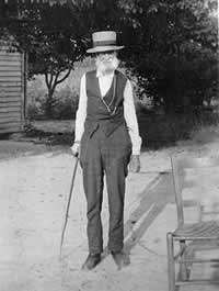 In his elder years, with a full white beard and a cane.
