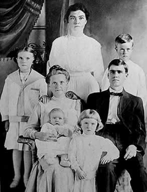 Jonah, his mother, his wife and their four children in a studio portrairt.