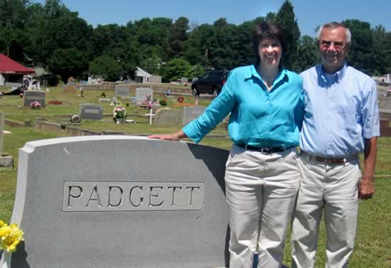 On a sunny day in May, Jim and Kathy stand beside a Padgett tombstone.