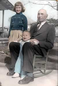 The old man in a rocking chair, in the yard, in suit and tie, with two young grandkids.