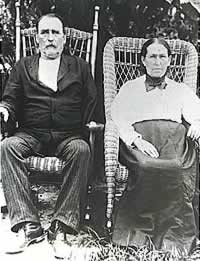 Solemn old couple in wicker chairs