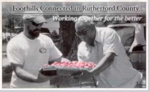 """Image of vendor and customer at farmers market admiring tray of tomatos. Text: """"Foothills connected in Rutherford County. Working together for the better."""""""