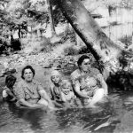 Ladies and kid in house clothes bathing in creek
