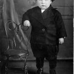Chubby boy from about 1910 in photographers studio