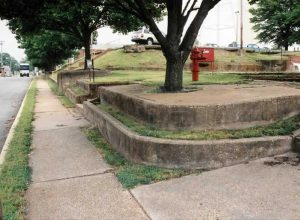 At street corner showing sidewalk and adjacent 3 to 4-foot retaining wall on which mill workers sat.