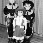 'Cowgirl,' age about 4, backed up by her two brothers, also in western garb