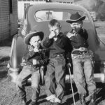 "Three ""cowpokes"" aiming their capbusters at photographer"