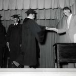 Graduate on stage receiving diplomas