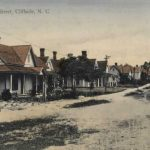 1920s dirt street with row of home