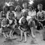School girls and the Huss family seated on sandy riverside