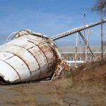 Water tower collapsed on ground, being removed for scrap