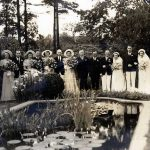 Large wedding party around fish pond