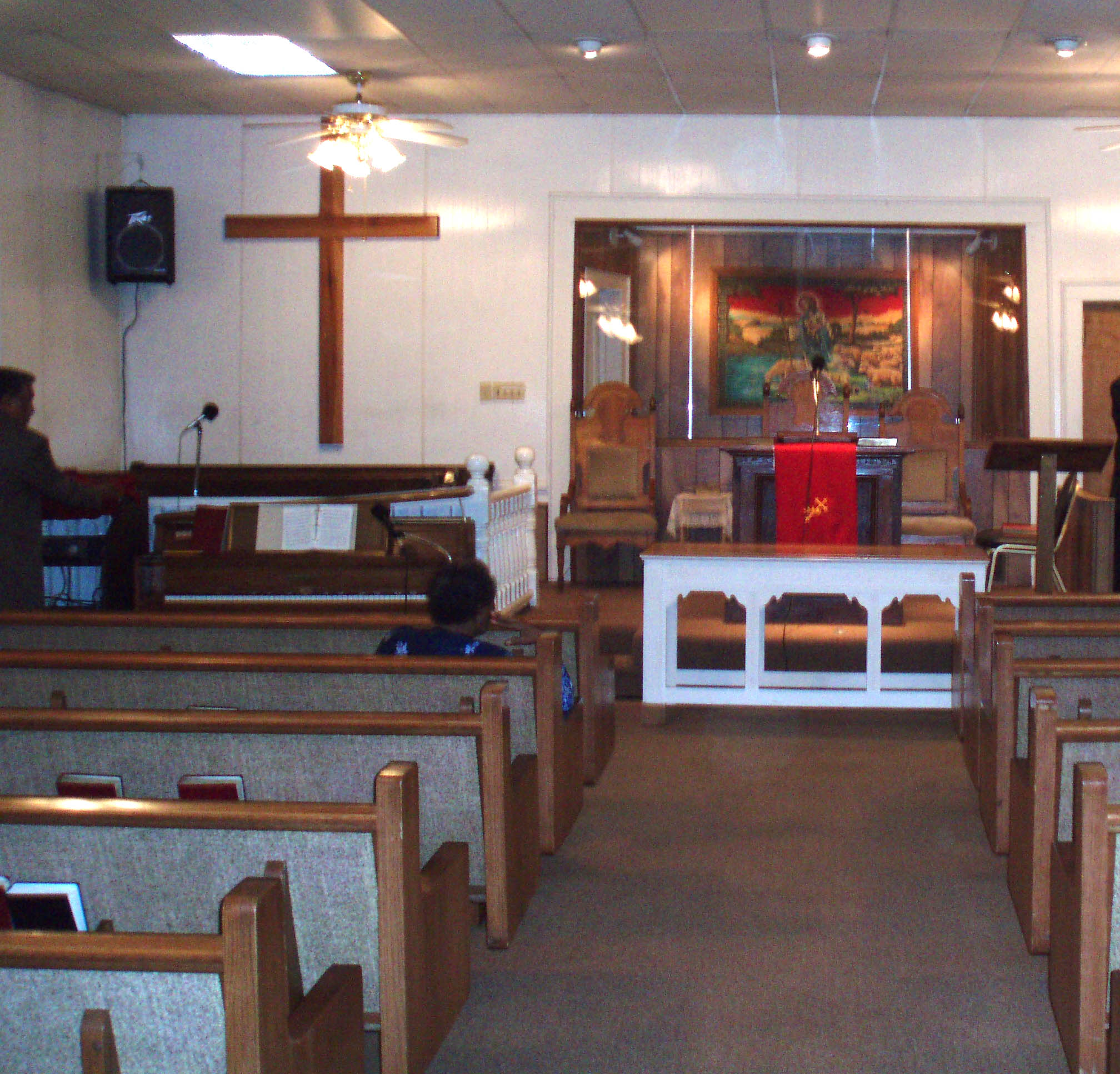 Looking toward front of sanctuary with pews on both sides of the aisle.