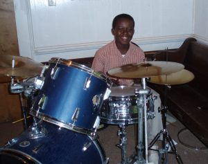Jeremy Vernon, young teen playing drums.