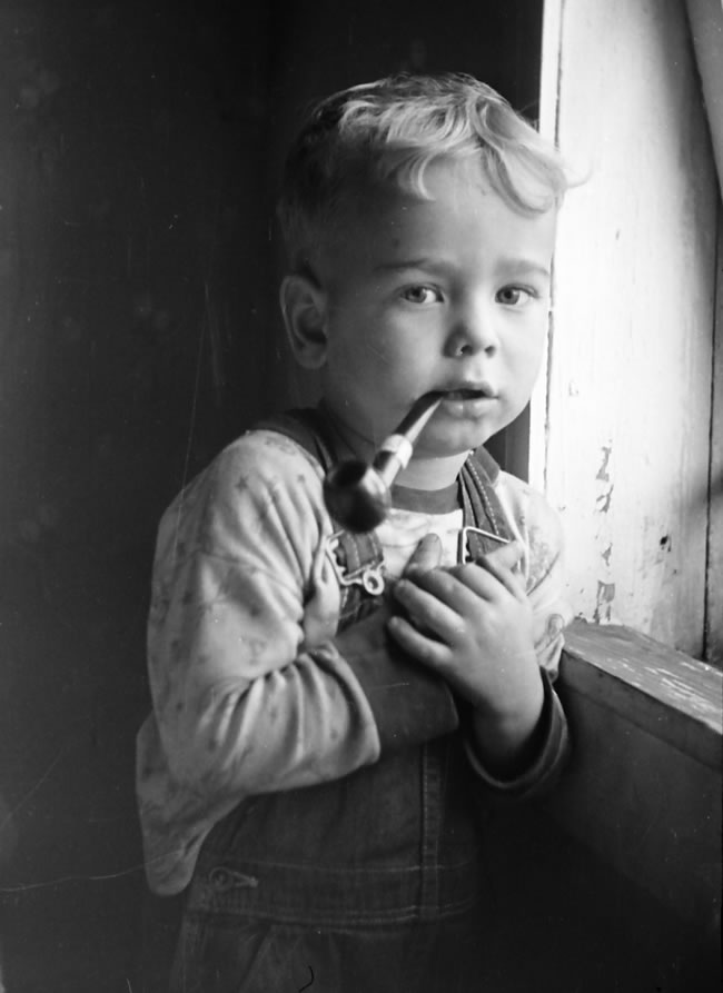 He's three or four with pipe in mounth, standing beside a window. The soft light makes it a beautiful portrait of an innocent child.