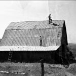 Tall, steep tin-roofed barn.