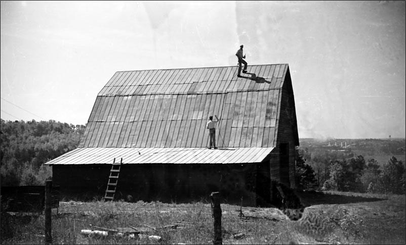 Tall, steep tin-roofed barn.