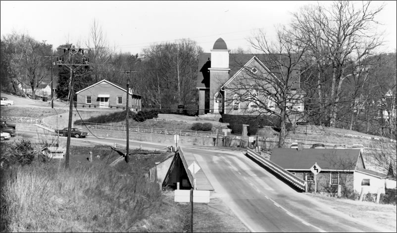 We see a landscape that includes the river bridge in the foreground, and the roads curve in front of the church.