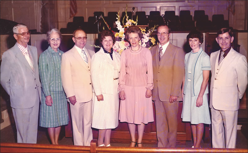 There are eight pastors and wives standing in nave of the church.