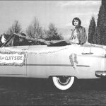 "She sits atop the back seat of a Ford convertible decorated with streamers and a sign reading ""Miss Cliffside."""