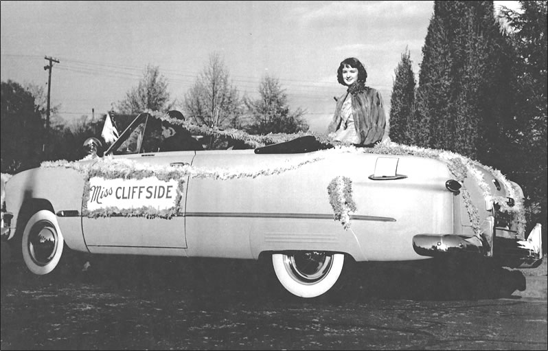 """She sits atop the back seat of a Ford convertible decorated with streamers and a sign reading """"Miss Cliffside."""""""