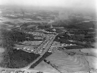 High aerial shot of Duke Village, the power plant and the countryside, a hodge-podge of fields and forests.