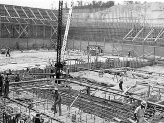 At an early stage of construction. Huge interior with workman on a lower floor pouring concrete onto grids of rebar.