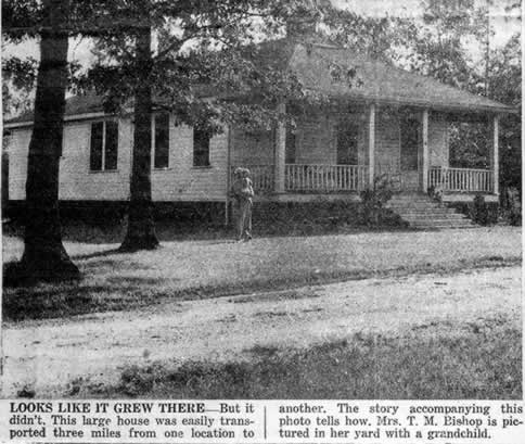 Caption reads 'Looks like it grew there, but it didn't. This large house was easily transported three miles from one location to another. The story accompanying this photo tells how. Mrs. T. M. Bishop is pictured in her yard with a grandchild.'