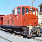 "It's a red diesel engine with the combination caboose/boxcar coupled in front. They're sitting idle in the CRR ""yards."""