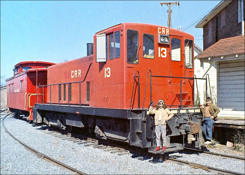 """It's a red diesel engine with the combination caboose/boxcar coupled in front. They're sitting idle in the CRR """"yards."""""""