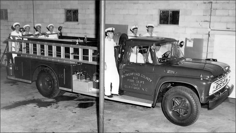 Nine firemen in their white coveralls and uniform caps are on and in the specially-built Ford ladder truck.