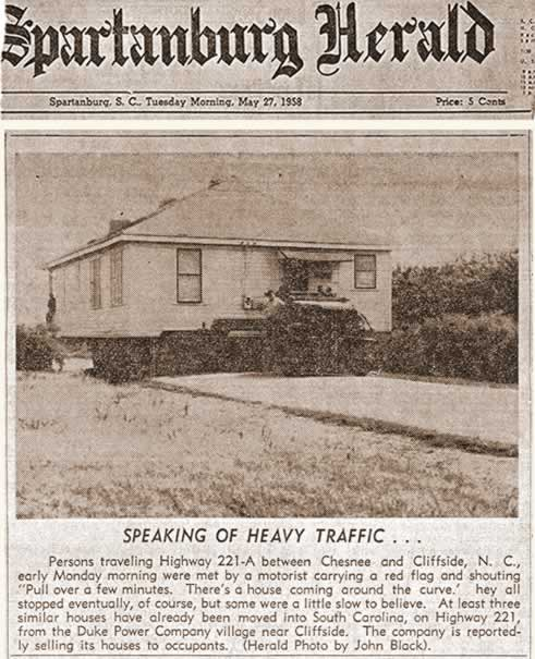 A clipping from the Spartanburg Herald, dated May 27, 1958, displaying a photo of house being moved on a narrow roadway.