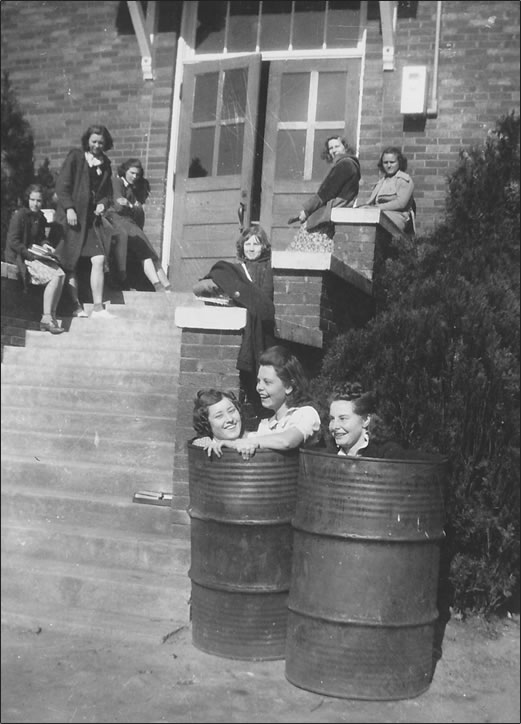 They at the school's back entrance. Two girls are in one 55-gallon metal drum, one is in another. Six other girls sit on steps' side columns.