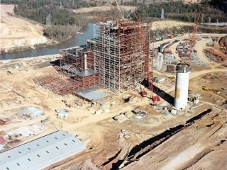 Large area of raw earth upon which the steel skeleton of the massive building, girdled with scaffolding.
