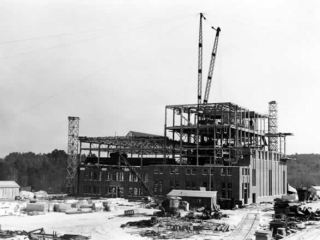 Plant under construction. Four stories or more of steelwork; brick has been laid on the exterior walls about half way up.