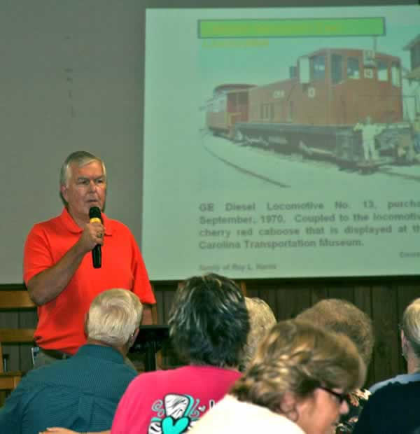 Wayne at the mike before a large projected photo of a CRR diesel engine.