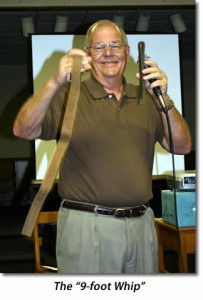 """Phillip White holds up the """"9-foot whip"""" (which is a belt actually about 3-feet long."""