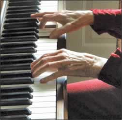 A closeup of her hands on the keys.