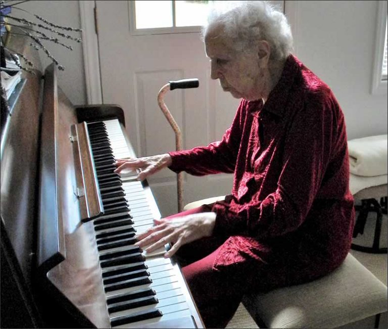 The elderly lady sits at they keyboard in her home.