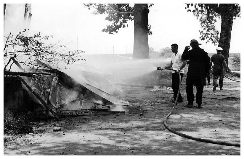 Spraying down smoking pile of remains of the old house.
