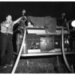 Night: Rear of firetruck with work lights on and hoses attached. Hot, sweaty fireman with jacket off, puffs on stump of cigar.
