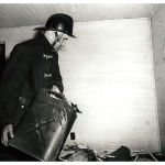 Inside empty room in house, fireman, preparing to set fire, sprinkles flammable liquid onto a small pile of trash. He's smoking a cigar.