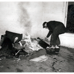 Fireman bends over trash setting it ablaze.