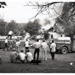 Daylight scene: Safely back from burning mill house, a dozen men and boys watch the fire's progress.