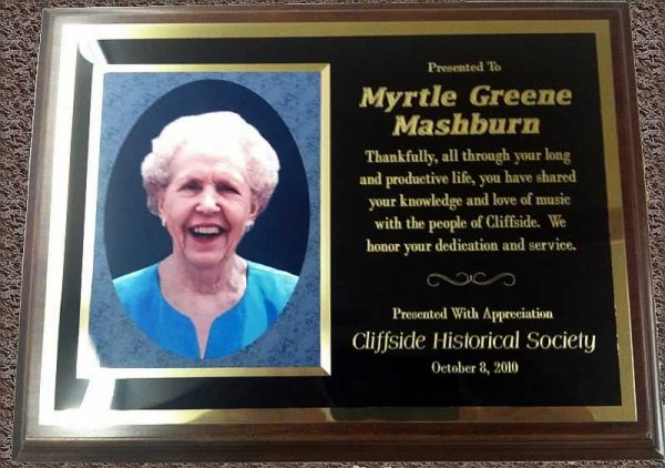 "The plaque, with a photo of Mrs Mashburn, reads, ""Presented to Myrtle Greene Washburn. Thankfully, all through your long and productive life, you have shared your knowledge and love of music with the people of Cliffside. We honor your dedication and service. Presented with appreciation. Cliffside Historical Society. October 8, 2010."""