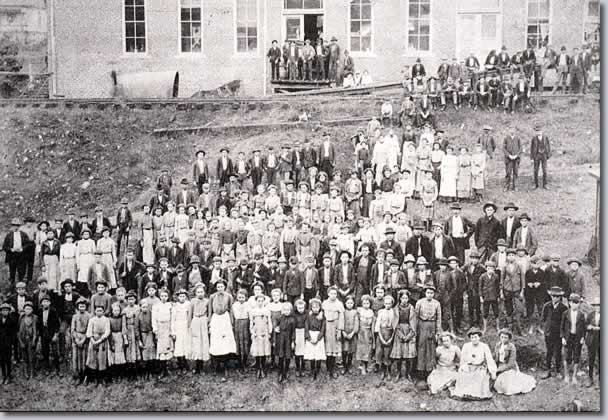 Perhaps 125 workers (men, women and children) grouped outside mill for photo.