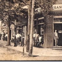 "Old picture postcard, labeled ""First National Bank, Forest City, N. C."" Many men lining the tree shaded sidewalk. Bank in foreground."